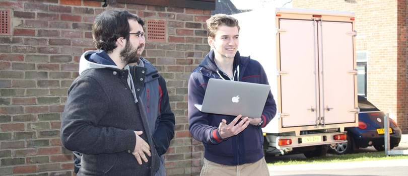 Researchers holding a laptop outside at Oxford's Department of Engineering Sciences